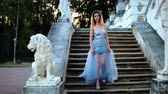 excitação : Attractive girl with black brows and curly hair in silver and blue dress in high heeled shoes stands on stairs with stone balustrade near lion statue and poses during photoshoot in antique estate.