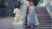 excitação : Attractive girl in silver and blue dress in high heeled shoes stands on stairs with stone balustrade near lion statue and gets ready to pose during photoshoot in antique estate.