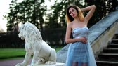 excitação : Attractive girl in silver and blue dress in high heeled shoes stands on stairs with stone balustrade near lion statue posing during photoshoot in antique estate. Stock Footage