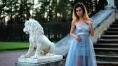 excitação : Attractive girl in silver and blue dress stands on stairs with stone balustrade near lion statue posing with hand on neck and turns to the left during photo shoot in antique estate.