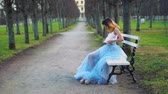 excitação : Attractive girl in silver and blue dress sits on bench in parkway adjusting dress, puts on white tank top and gets ready to pose during photo shoot.