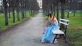 excitação : Attractive girl in silver and blue dress sits on bench in parkway putting on high heeled shoes and gets ready to pose during photo shoot. Side view. Stock Footage