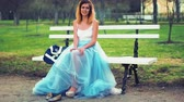 excitação : Attractive girl in silver and blue dress sits on bench in parkway putting on high heeled shoes, poses and stands up from bench during photo shoot. Front view.