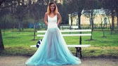 make photo : Attractive girl in white and blue dress stands near bench in parkway adjusts dress with visible underwear and talks looking at camera during photo shoot. Front view.