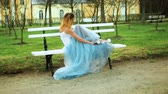 excitação : Attractive girl in white and blue dress sits on bench in parkway putting legs in high heeled shoes on bench during photo shoot. Stock Footage