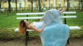 posh : Attractive girl in white and blue dress lies on bench with legs in high heeled shoes riased on back of bench in parkway posing during photo shoot.
