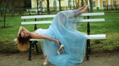 posh : Attractive girl in white and blue dress lies on bench, moves bare feet and handles high heeld shoes posing during photo shoot. Stock Footage