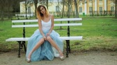posh : Attractive skinny girl in silver and blue dress sits on bench in parkway in high heeled shoes with knock knees and uncovered legs preparing to pose during photo shoot. Front view.