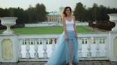 впечатляющий : Attractive skinny girl in white and blue dress stands near white stone balustrade smiling and posing during photo shoot. Стоковые видеозаписи