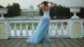 make photo : back view of attractive skinny girl in white and blue dress who stands near white stone balustrade posing during photo shoot.