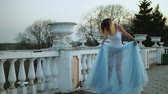 excitação : Attractive skinny girl in white and blue dress stands near white stone balustrade smiling and posing during photo shoot. Stock Footage