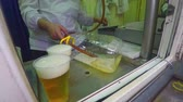 Male hand pouring of rubber tubing fresh beer in plastic cups and a bottle
