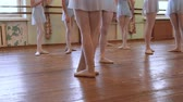 frayed : Legs of ballerinas in blue suits standing on floor and walk away during ballet class.