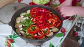 uzbek : Hands of white cook add pepper into large cooking pot with vegitables.