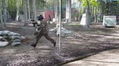 bojiště : Man in protective uniform and mask with gun in right hand runs playing paintball. Slow motion