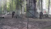 Paintball players run and shoot at each other and then hide behind tree and shield Stock Footage
