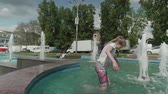 Girl jumps into fountain and walks through sprays of water in it. Slow-motion view Stock Footage