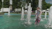Slow motion view of girl in fountain touching sprays of water and then goes out of it. Stock Footage