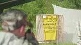 operador : Blur back view of man shooting at yellow aim with animals drawn on it. Man is at left side.