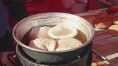 mutton : Meat pasty is being fried outside on open fire in a pot with oil Stock Footage