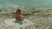 no idea : Young blonde girl in bathing suit sits alone on a rocky beach and makes up the word Bitcoin