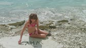 dilek : Young blonde girl in bathing suit sits alone on stony beach and makes out the stones of question Why