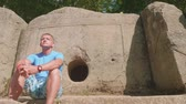 mítico : Caucasian man sits thoughtfully next to the ancient dolmen