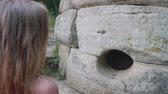 ecclesiastic : Young caucasian blonde teenager look at the ancient dolmen. Back view