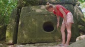 ecclesiastic : Young caucasian girl standing and touching an ancient dolmen