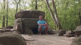 interessante : Caucasian man sits thoughtfully next to the ancient dolmen