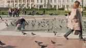 saturado : BARCELONA, SPAIN - CIRCA NOVEMBER 2017: Guy takes picture of his friend among pigeons on Catalonia square ful of people and pigeons