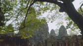 кхмерский : View of Angkor Wat temple trough green leaves of trees