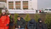 significar : People are sitting on bench with bill saying Metrostroi and Moscow Government