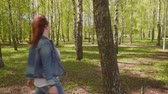 ангельский : Young woman comes up to tree puts hand on it, turns around her head and smiles looking at camera