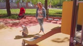 bem aventurado : Mom watches her son sliding down from playgournd slide on playground Stock Footage