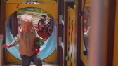 ангельский : Little blond toddler approaches camera playing on playground