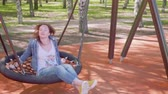ангельский : Woman sits on swing on playgorund and looks at camera Стоковые видеозаписи