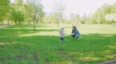 ангельский : Blond toddler runs to his mom sitting on green grass