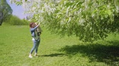 como : Mom and son smell flowers on trees and laugh Stock Footage