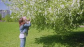lovable : Mom and son smell flowers on trees and laugh Stock Footage
