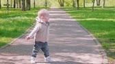 ангельский : Little blond boy walks on path in park
