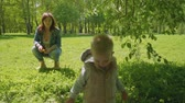 ангельский : Mom watches little son playing on green grass in park