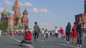 worldcup : Tourists and football fans walk on Red square in moscow. guy makes photo sitting on knees