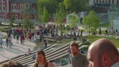 fãs : MOSCOW - CIRCA JUNE, 2018: Tourists and football fans walkn in Zaryadye Park in Moscow Vídeos