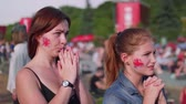 worldcup : Girls with Britain flag on cheeks watch football match in fan zone