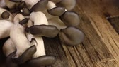 soupon : Many raw unpeeled mushrooms on brown wooden table. Stock Footage