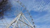 Underside view of a ferris wheel against blue sky with clouds. Steadicam shot.