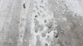 Treads and footprints in snow, city street covered in snow. Steadicam shot.