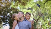 Happy father with children having fun and taking selfie outdoors Стоковые видеозаписи