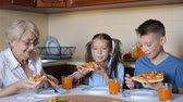 Grandmother with grandchildren are eating pizza at home